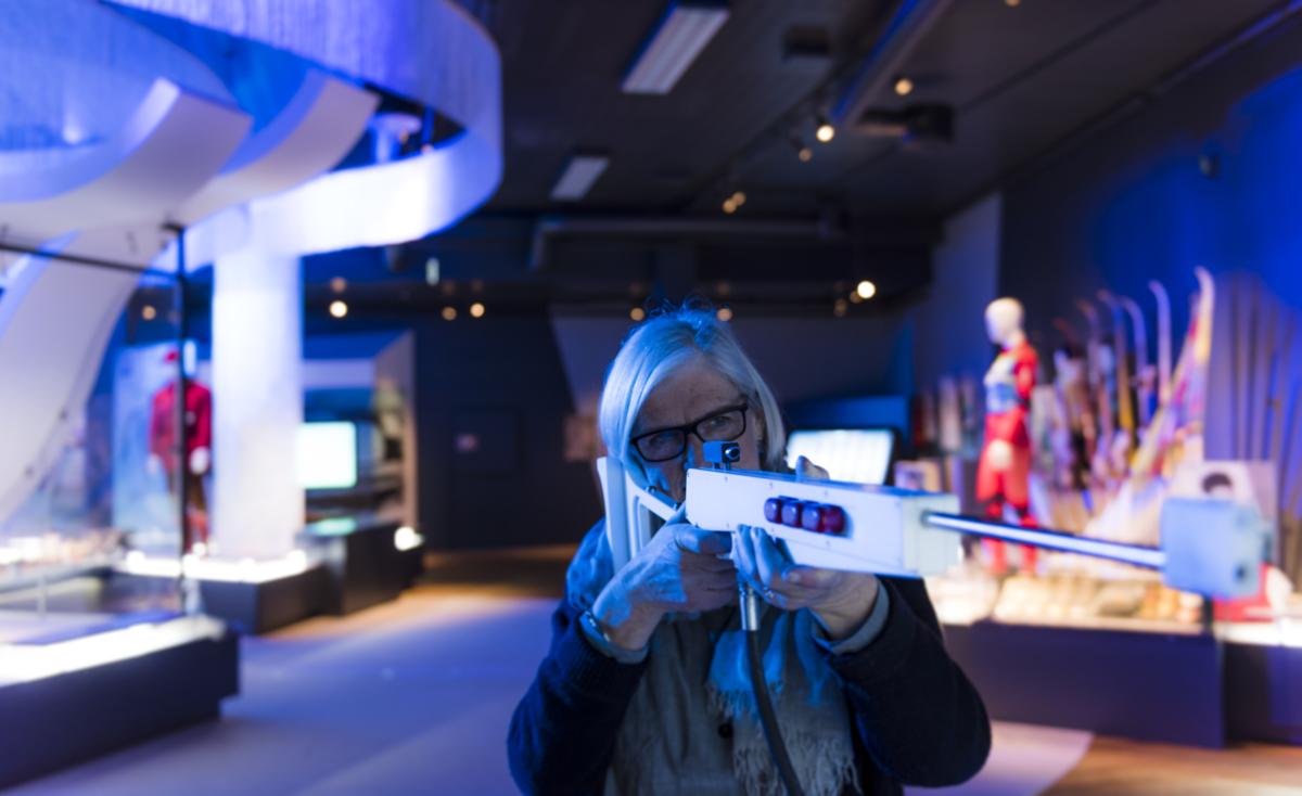 Dame med gevær i skiskyttersimulatoren i Norges Olympiske Museum.