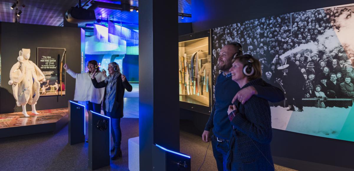 Gjester ser på skjerm med hodetelefoner og smiler med hendene i været.