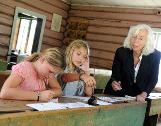 Jenter og lærer på Skolestua i friluftsmuseet på Maihaugen på Lillehammer.