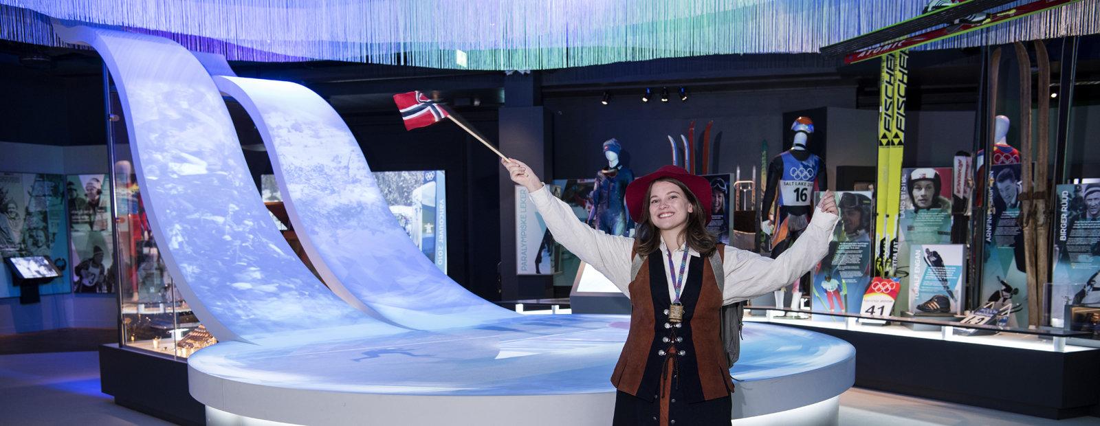 Dame kledd i ullkjole og med norsk flagg i hånda, sekk på ryggen og kubjelle rundt halsen.