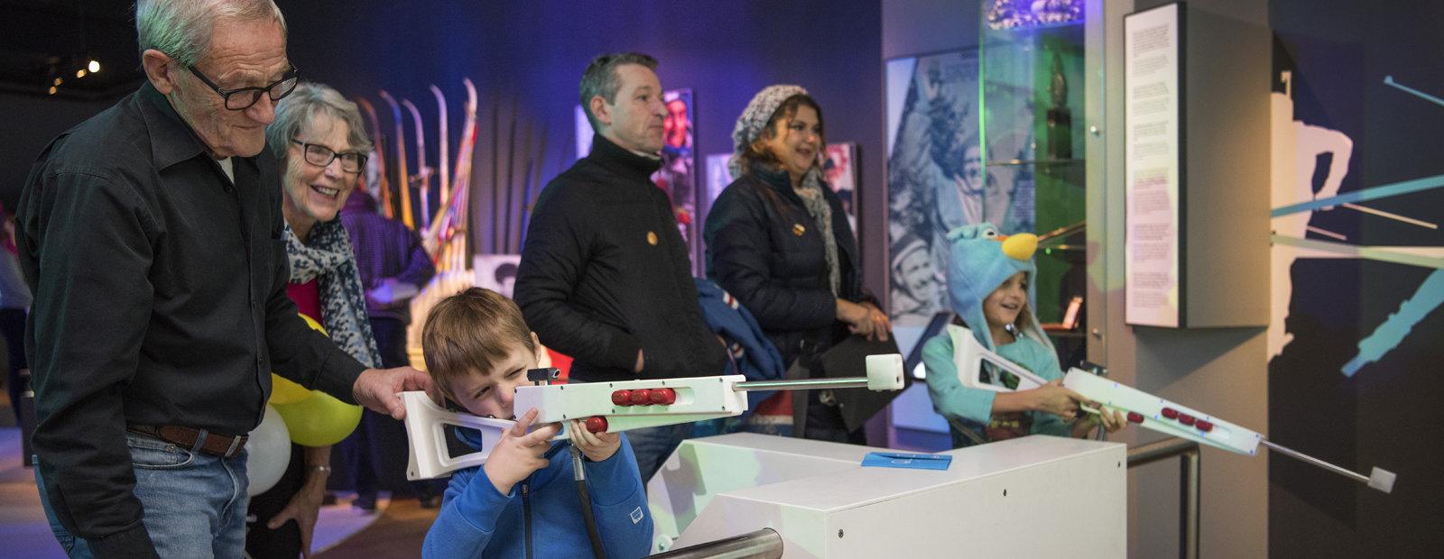Barn og voksne prøver skiskyttersimulator.