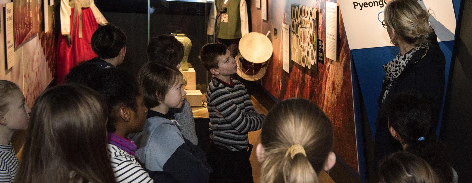 En omviser viser og forteller en gruppe barn i Norges Olympiske Museum på Lillehammer.