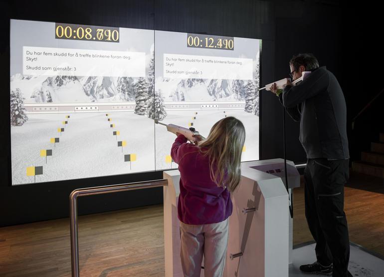 Mann og jente står og sikter med skiskyttergevær mot skjerm med vinterlandskap og skiskytterblink.